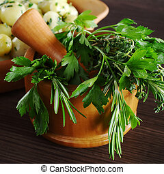 Fresh herbs (parsley, rosemary and thyme) in wooden mortar with pestle (Selective Focus, Focus on the front of the herbs)