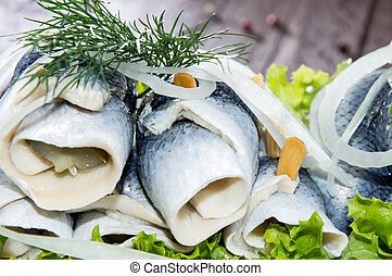 Fresh Herring Filet on a plate against wooden background