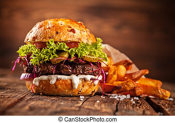 Fresh home-made hamburger served on wooded table with pomme...