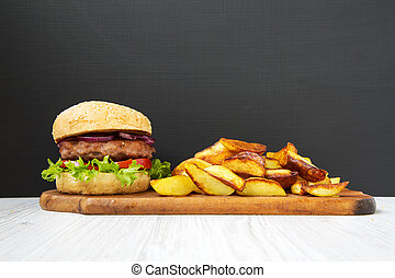 Fresh homemade burger with fried potatoes on wooden board. Closeup.