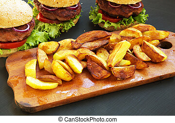Fresh homemade burgers with fried potatoes on wooden board. Closeup.