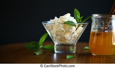 fresh homemade cottage cheese with honey in a glass bowl
