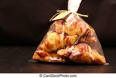 Fresh homemade French croissants with filling in a transparent cellophane bag with a tag on a black table