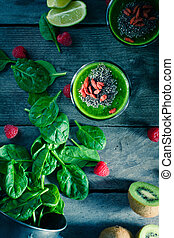 Fresh homemade green smoothie of baby spinach, kiwi, raspberry and lime sprinkled with chia seeds and goji berries top view.