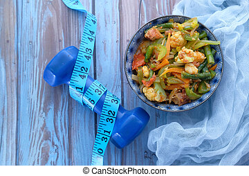 Fresh homemade salad in a plate with dumbbell on table
