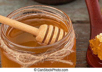 Fresh honey in the pot on a wooden background