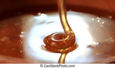 fresh honey pouring into a clay pot