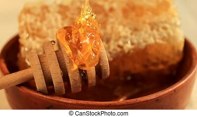 fresh honey with wooden dipper and honeycomb
