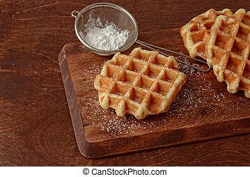 fresh hot Belgian waffles with icing sugar on a cutting ...