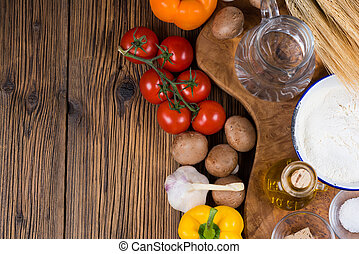 Fresh ingredients for a traditional pizza dough and topping with tomatoes, mushrooms and garlic on a board of olive wood with ears of grain in the background.