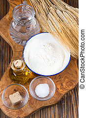 Fresh ingredients for a traditional pizza dough on a board of olive wood with ears of grain in the background.