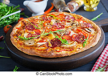 Fresh Italian pizza with chicken fillet, mushrooms, ham, salami, tomatoes, cheese on a black background. Italian food.
