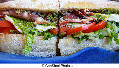 A fresh italian sub sandwich with meats, cheeses and pesto sauce
