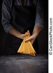 Fresh italian uncooked homemade pasta in female hands on...