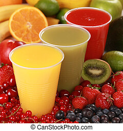 Cups with different kinds of juices surrounded by fresh fruits