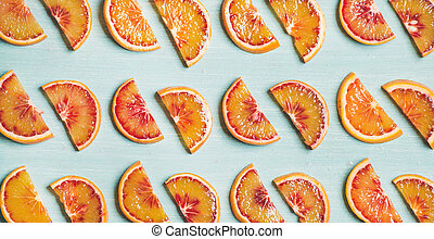 Fresh juicy blood orange slices over blue background, wide...