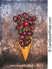 Fresh juicy cherry berries in a waffle cone on a dark old background, toned in retro style, top view