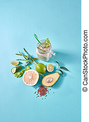 Fresh juicy detox green smoothies in glass cup with green vegetables and fruits on a blue paper background.