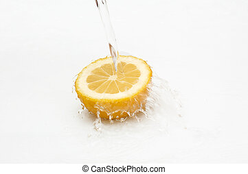 Fresh, juicy lemon in streaming water.