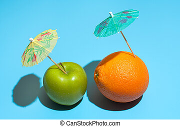 Fresh juicy orange and green apple with a cocktail umbrella isolated on blue background. Concept of Healthy eating and dieting. Travel and holiday concept
