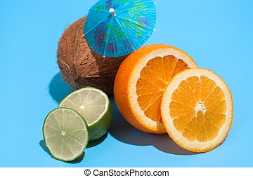 Fresh juicy orange, coconut and green lime with a cocktail umbrella isolated on blue background. Concept of Healthy eating and dieting. Travel and holiday concept