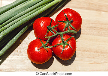 Fresh juicy tomatoes on wooden chopping board