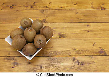 Fresh kiwi fruits piled in a bowl on a table