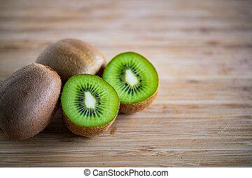 Fresh kiwifruit on wooden cutting board.