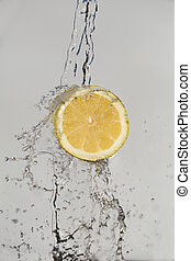 Fresh lemon and water splash on white background.