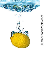 Fresh lemon dropped into water with bubbles isolated on white