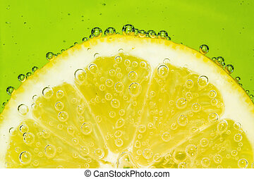 Fresh lemon in soda water covered with bubbles on green...