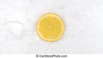 Fresh lemon on the top view the water is pouring on a white background