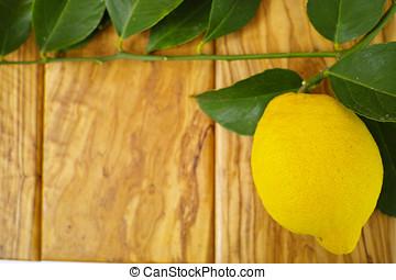Fresh lemon with leaves on olive wood