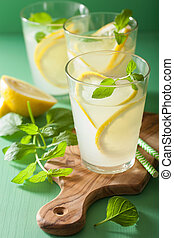 fresh lemonade drink with mint in glasses