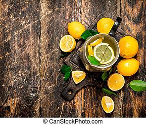 Fresh lemonade in a jug with slices of lemon .