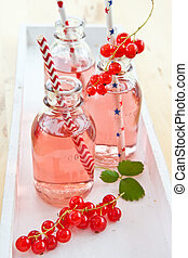 Fresh lemonade with red currant in little vintage bottles