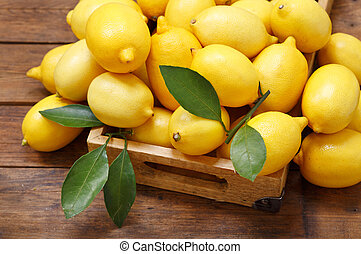 fresh lemons in a wooden box, top view