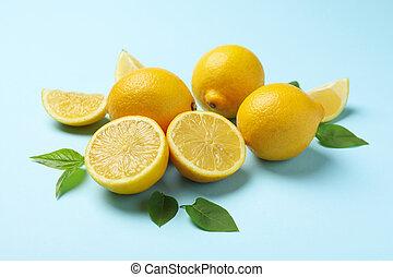 Fresh lemons with leaves on blue background, close up. Ripe fruit