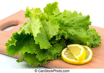 Fresh lettuce with slices of lemon on the cutting board