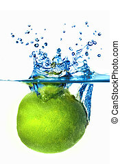 Fresh lime dropped into water with bubbles isolated on white