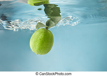 Fresh lime in water isolated on a blue background
