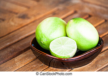 Fresh lime wholes and slice on wood background