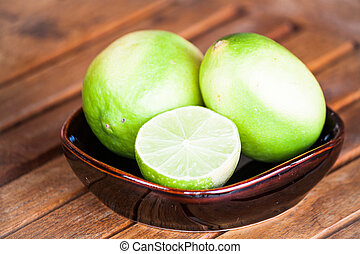 Fresh lime wholes and slice on wood table