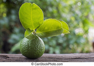 Fresh lime with leaves on wooden background