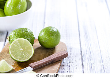 Fresh Limes (detailed close-up shot) on wooden background...