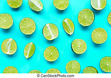 Fresh limes on blue background. top view