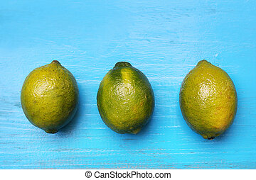 Fresh limes on wooden blue background