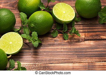 Fresh limes on wooden table, Top view, background.