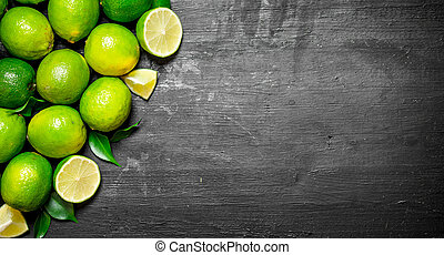 Fresh limes with green leaves. On a black chalkboard.