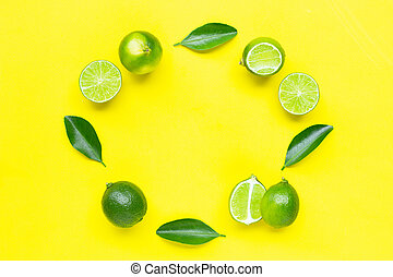 Fresh limes with leaves on yellow background.
